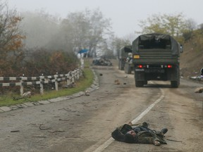 Military vehicles of the Russian peacekeeping forces drive by the body of a person in military uniform, who was killed during a conflict over the breakaway region of Nagorno-Karabakh.