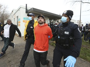 Adamson BBQ owner Adam Skelly is led away from his restaurant by Toronto Police on Nov. 26.