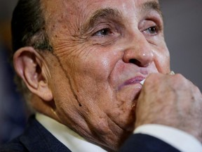 Former New York City Mayor Rudy Giuliani, personal attorney to U.S. President Donald Trump, wipes away sweat as he speaks about the 2020 U.S. presidential election results during a news conference in Washington, U.S., November 19, 2020.