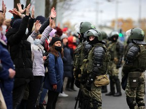 Law enforcement officers block protesters during a march of opposition supporters from central Minsk to a site of Stalin-era executions just outside the capital on November 1, 2020.