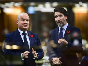 In the multiple-exposed image Conservative Leader Erin O'Toole, left, asks a question and Prime Minister Justin Trudeau answers during question period in the House of Commons on Parliament Hill in Ottawa on Wednesday, Nov. 4, 2020.