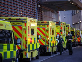 NHS workers walk next to a cue of ambulances outside the Royal London Hospital, in London, Britain January 12, 2021.