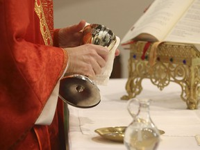 Father Peter Turrone performs Palm Sunday mass and the Eucharist - throughly cleaning the chalice - at the Newman Centre Catholic chapel on St. George St. before an empty church. It is a the beginning of Holy Week leading up to Good Friday and Easter next Sunday on Sunday April 5, 2020.