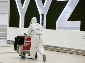 A passenger is covered head to toe at the international arrivals area at Pearson International Airport on January 26, 2021. News that vaccines will not necessarily end the COVID nightmare has the potential to ruin travel plans for the second half of 2021.