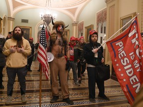 Supporters of U.S. President Donald Trump, including member of the QAnon conspiracy group Jake Angeli, aka Yellowstone Wolf, centre, enter the U.S. Capitol on Jan. 6, 2021, in Washington, D.C.
