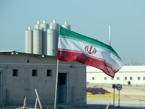 An Iranian flag flutters in front of Iran's Bushehr nuclear power plant.