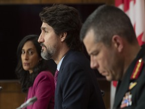 Public Services and Procurement Minister Anita Anand and Major General Dany Fortin look on as Prime Minister Justin Trudeau responds to a question during a news conference in Ottawa, Monday, Dec. 7, 2020.