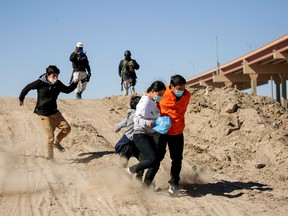 Migrants from Central America flee the Mexican National Guard in Ciudad Juarez, on February 5, 2021, to cross the Rio Bravo and request asylum in El Paso, Texas.