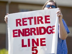 Lauren Sargent, of Ann Arbor, Mich. takes part in a protest before an Enbridge Line 5 public information session in a file photo from Holt, Mich., in July 2017.