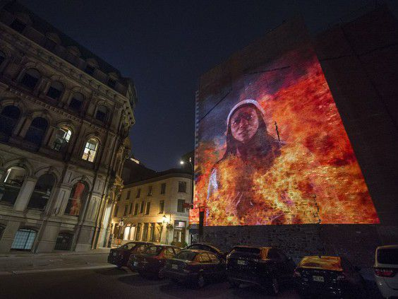 An image depicting Angelique is shown in a video projection in Montreal.