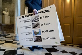 Senator Ron Johnson, a Republican from Wisconsin, carries signs from the Senate Chamber at the U.S. Capitol on Wednesday, March 3, 2021.