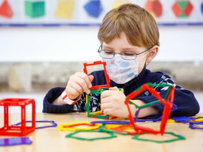 A child plays with colourful plastic blocks kit in a childcare environment.