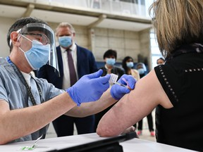 Ontario Premier Doug Ford, back centre, watches as a doctor administers the coronavirus vaccine to a nurse at a mass COVID-19 vaccination clinic in Mississauga, Ont., on March 1.