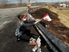 Care worker and first responder Alicia Cunningham adjusts a Canadian flagat a makeshift memorial for slain RCMP Const. Heidi Stevenson.