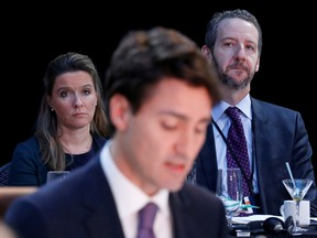 Katie Telford, back left, and Gerald Butts, back right, listen as Prime Minister Justin Trudeau speaks at a First Ministers meeting in Ottawa, in 2016.