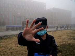 In this Feb. 3, 2021, file photo, a security person moves journalists away from the Wuhan Institute of Virology after a World Health Organization team arrived for a field visit.