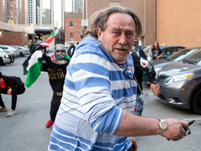 A pro-Israel supporter flees during a brawl with pro-Palestine supporters following a demonstration against the current violence in Gaza in Toronto on Saturday, May 15, 2021.