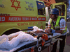 Rescue workers evacuate an injured youngster in the southern Israeli city of Sderot on May 12, 2021.