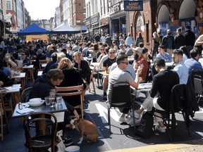 People packed on a London restaurant patio as COVID lockdown restrictions eased in Britain, April 24, 2021. In the space of three months, the U.K.'s daily average death toll dropped from 1,244 to 26; it is now at 13.