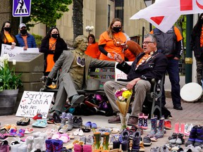 Elder Junior Peter Paul (sitting) points to a Sir John A. MacDonald statue next to 215 pairs of children's shoes placed in remembrance of the bodies discovered at the Kamloops Indian Residential School in British Columbia during a ceremony in Charlottetown, on Monday, May 31.