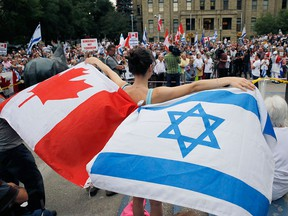 A participant waves Canadian and Israeli flags at a pro-Israel rally at Calgary city hall in a file photo from July 31, 2014. Canada has announced it is boycotting the Durban IV conference in New York this September due to anti-Semitism and the anti-Israel nature of the original event in 2001.