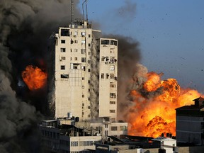 Smoke and flames rise from a tower building as it is destroyed by Israeli air strikes amid a flare-up of Israeli-Palestinian violence, in Gaza City on May 12, 2021.