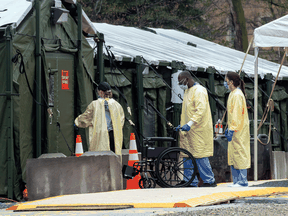 Staff enter the mobile field hospital set up to handle COVID-19 patients at Sunnybrook Hospital in Toronto. After graduating medical school, doctors in Canada must complete practical training of two years for family doctors and five for specialists.
