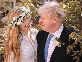 British Prime Minister Boris Johnson, right, poses with his wife Carrie Johnson in the garden of 10 Downing St., following their wedding at Westminster Cathedral, in London, on May 29.