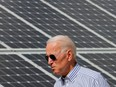 Now-U.S. president Joe Biden walks past solar panels while touring the Plymouth Area Renewable Energy Initiative in Plymouth, New Hampshire in June, 2019.