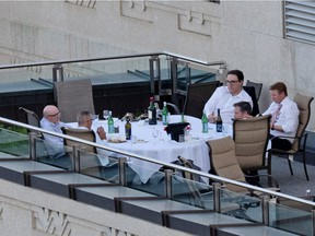 Premier Jason Kenney initially defended the patio dinner pictured here last week, saying it was in line with the province's outdoor gathering rule that permits 10 people as long as they are two metres apart. From the top right is Environment and Parks Minister Jason Nixon, Health Minister Tyler Shandro, Premier Jason Kenney, Finance Minister Travis Toews and an unidentified staffer.