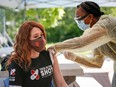 """Olympic medallist Clara Hughes receives a second dose of a COVID-19 vaccine at a community vaccination clinic at the Stoney Nakoda First Nation health services centre in Morley, Alta., on June 17, 2021. Although there are minor structural differences between Pfizer and Moderna vaccines, """"their effects on the immune system are identical for all intents and purposes,"""" writes infectious diseases expert Dr. Zain Chagla."""