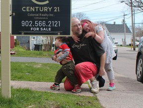 Jeff Gallant crouches with his children outside his rental unit in Charlottetown, two weeks before receiving an eviction notice.