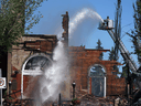 A firefighter douses the remains of St. Jean Baptiste Parish church in Morinville, Alta., which burned to the ground on June 30, 2021.