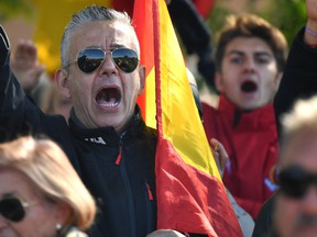 A supporter of Francisco Franco gestures as people gather near Mingorrubio cemetery before his exhumation on October 24, 2019 in El Pardo neighborhood, in Madrid, Spain.