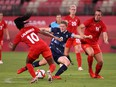 Ellen White (No. 9) of Team Great Britain shoots whilst under pressure from Ashley Lawrence (No. 10) and Vanessa Gilles (No. 14) of Team Canada during the Women's Group E match between Canada and Great Britain at the Tokyo 2020 Olympic Games at Kashima Stadium on July 27, 2021 in Kashima, Ibaraki, Japan.