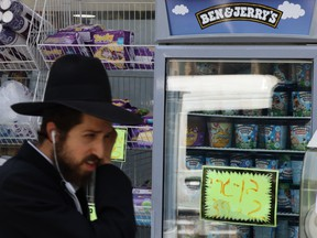 An ultra-Orthodox Jewish man walks by Ben and Jerry's ice cream in Jerusalem on July 20.