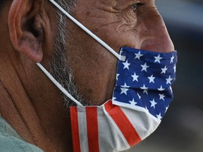 In this photo taken on July 19, 2021, a man wears an American flag face mask on a street in Hollywood, California, on the second day of the return of the indoor mask mandate in Los Angeles County due to a spike in COVID-19 cases.