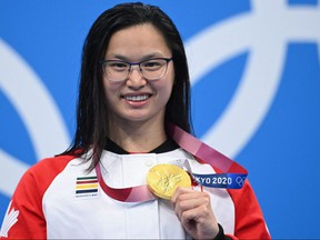 Gold medallist Canada's Maggie Mac Neil poses with her medal on the podium after the final of the women's 100-metre butterfly swimming event during the Tokyo 2020 Olympic Games at the Tokyo Aquatics Centre in Tokyo on July 26, 2021.