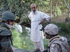 A Canadian soldier, right, speaks to a resident of Bazaar-i-Panjwaii in Afghanistan with the help of an interpreter, left, on August 11, 2008.