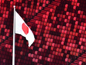 An overview shows the Japanese national flag with empty stands during the opening ceremony of the Tokyo 2020 Olympic Games.