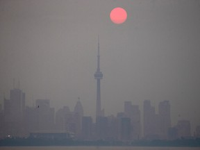 The sun rises through a cover of wildfire smoke above the CN Tower and downtown skyline in Toronto, Ontario, Canada July 20, 2021.
