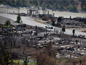 An RCMP vehicle drives past the remains of vehicles and structures in Lytton on July 9, 2021, after a wildfire destroyed most of the village on June 30.