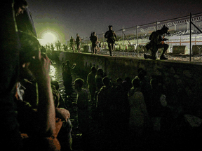 British and Canadian soldiers stand guard near a canal as Afghans wait outside the foreign military-controlled part of the airport in Kabul, hoping to flee the country, on August 22, 2021.