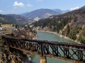 The charred remnants of the rail bridge, destroyed by a wildfire on June 30, is seen during a media tour by authorities in Lytton, B.C., July 9, 2021.
