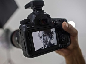 A woman is seen in the screen of a photo camera during a photo shoot to make content for her OnlyFans profile.(Photo by CRISTIAN HERNANDEZ/AFP via Getty Images)