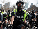 Toronto police officers enforce COVID-19 restrictions at an anti-lockdown protest, April 10, 2021.