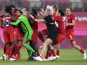 Canada's players celebrate after defeating the United States 1-0 during a women's semifinal soccer match at the 2020 Summer Olympics, Monday, Aug. 2, 2021, in Kashima, Japan.