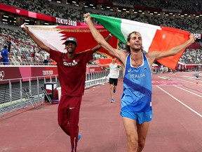 Gold medalist Mutaz Essa Barshim (L) of Team Qatar and silver medalist Gianmarco Tamberi of Team Italy celebrate on the track following the Men's High Jump Final during the Tokyo 2020 Olympic Games at the Olympic Stadium in Tokyo on August 1, 2021. (Photo by Christian Petersen / POOL / AFP)