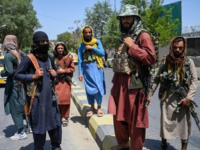 Taliban fighters stand guard along a street near the Zanbaq Square in Kabul on August 16, 2021.