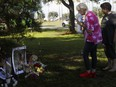 Two women pay their respects at a makeshift memorial dedicated to Gabby Petito, near the North Port, Fla. city hall, on Sept. 20, the day before the body found in Wyoming was identified as Gabby Petito.